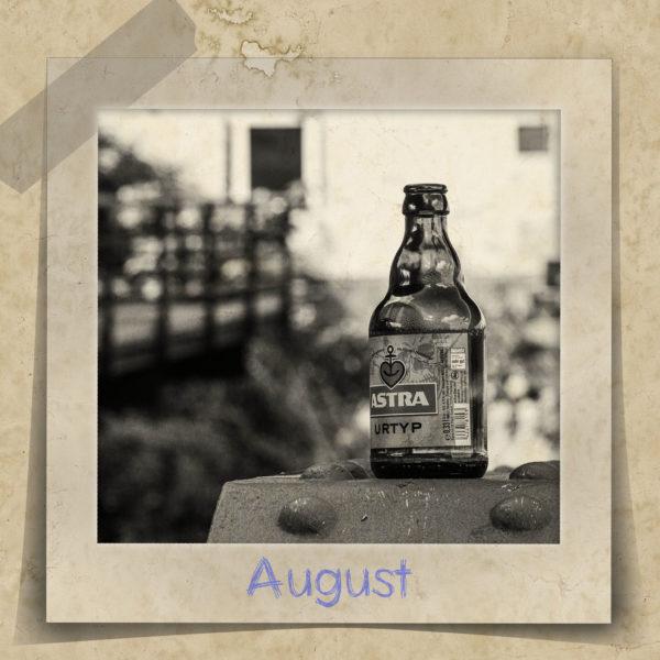 Leere Bierflasche der Marke Astra auf einem Geländer an einem Fähranleger.